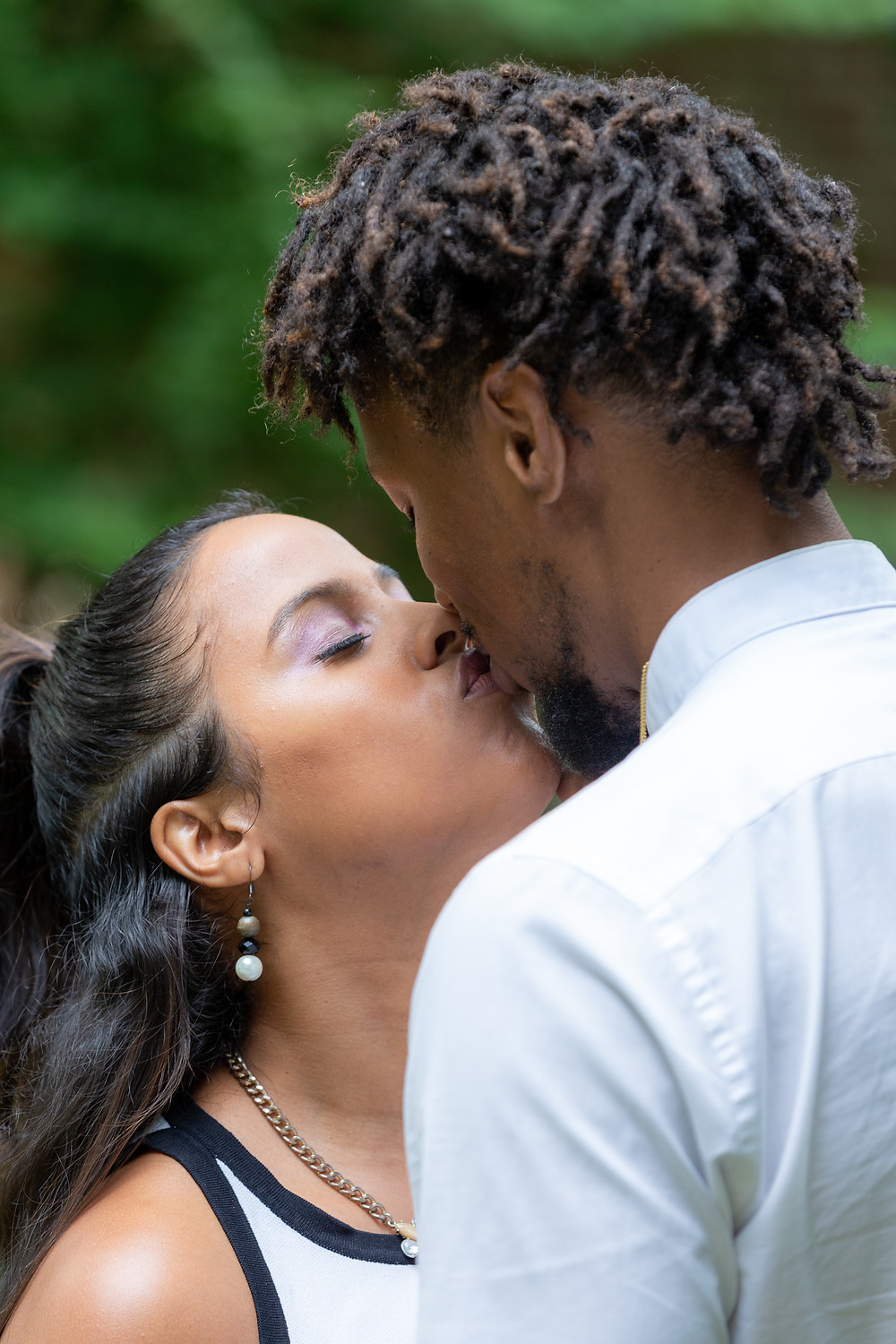 Couple share a kiss during their engagement session at The Carlyle House in Old Town Alexandria, Virginia.