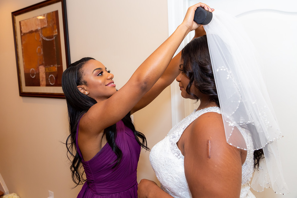 Jordyn's bridesmaid puts on the wedding veil before the ceremony in Fairfax, Virginia.