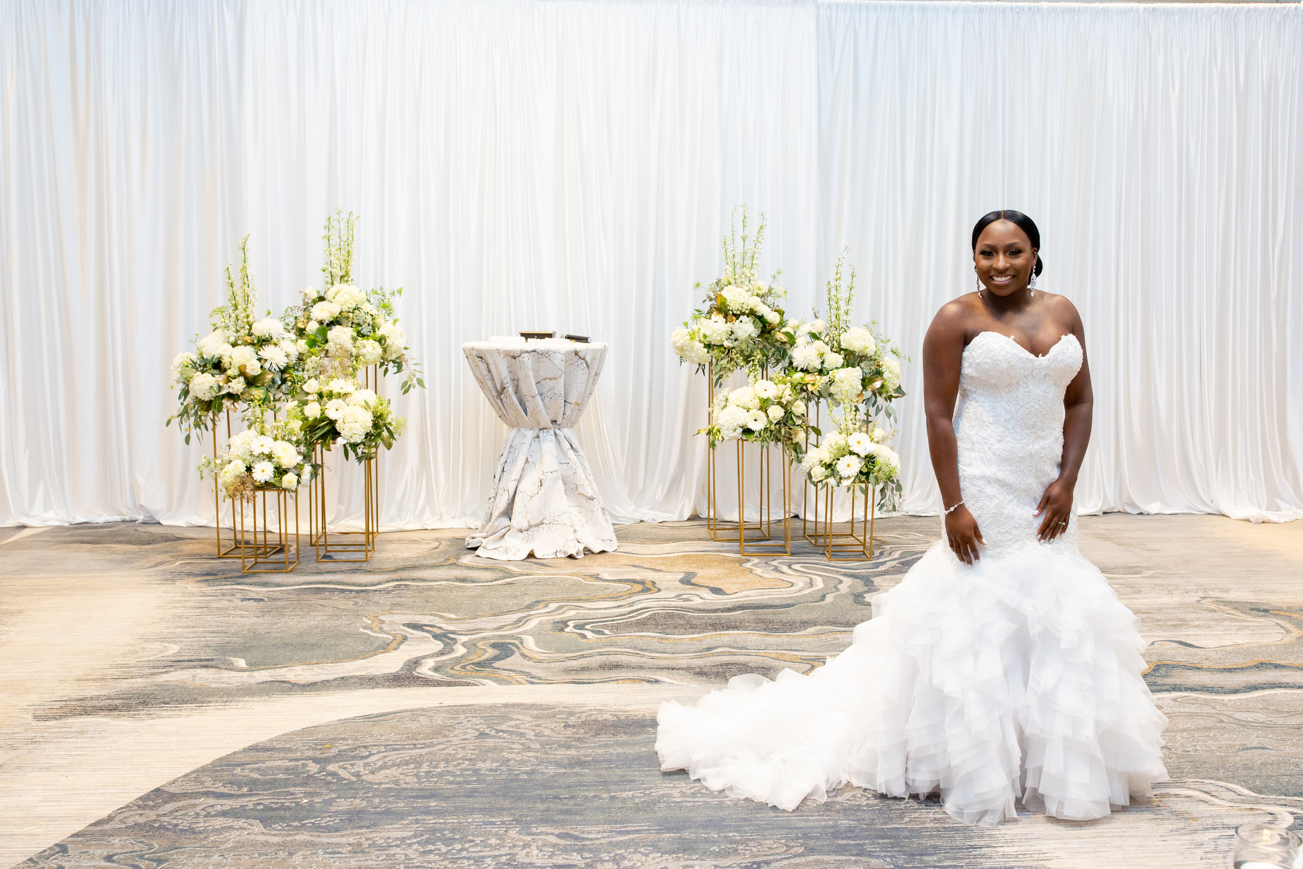 The bride poses in the ceremony area before guests arrive for the wedding ceremony at the Hilton Main in Norfolk, Virginia.