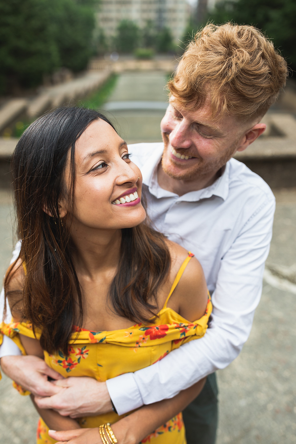John and UK embrace each other during the engagement session at Meridian Hill Park in Washington DC.