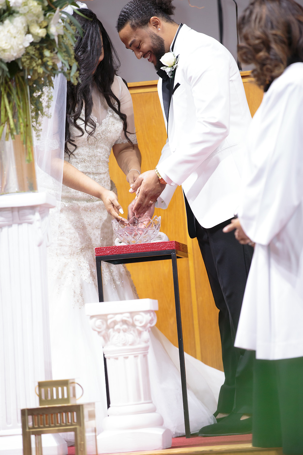 The bride and groom participate ni the hand washing ceremony during the wedding ceremony at the Alfred Street Baptist Church in Alexandria, Virginia.