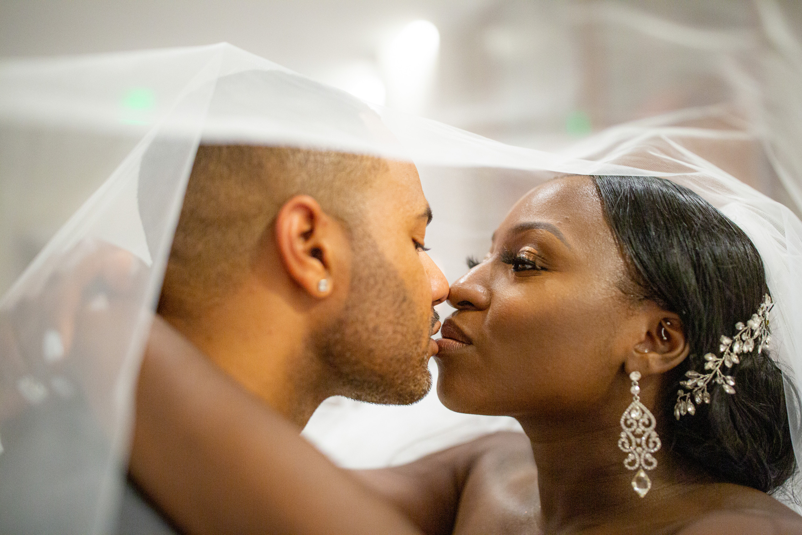 The bride and groom share an intimate moment under the bride's veil during the wedding reception at the Hilton Main in Norfolk, Virginia.