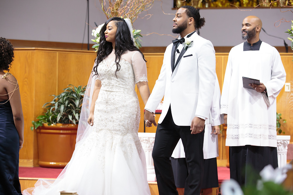 The bride and groom look on as the soloists perform during the wedding ceremony at the Alfred Street Baptist Church in Alexandria, Virginia.