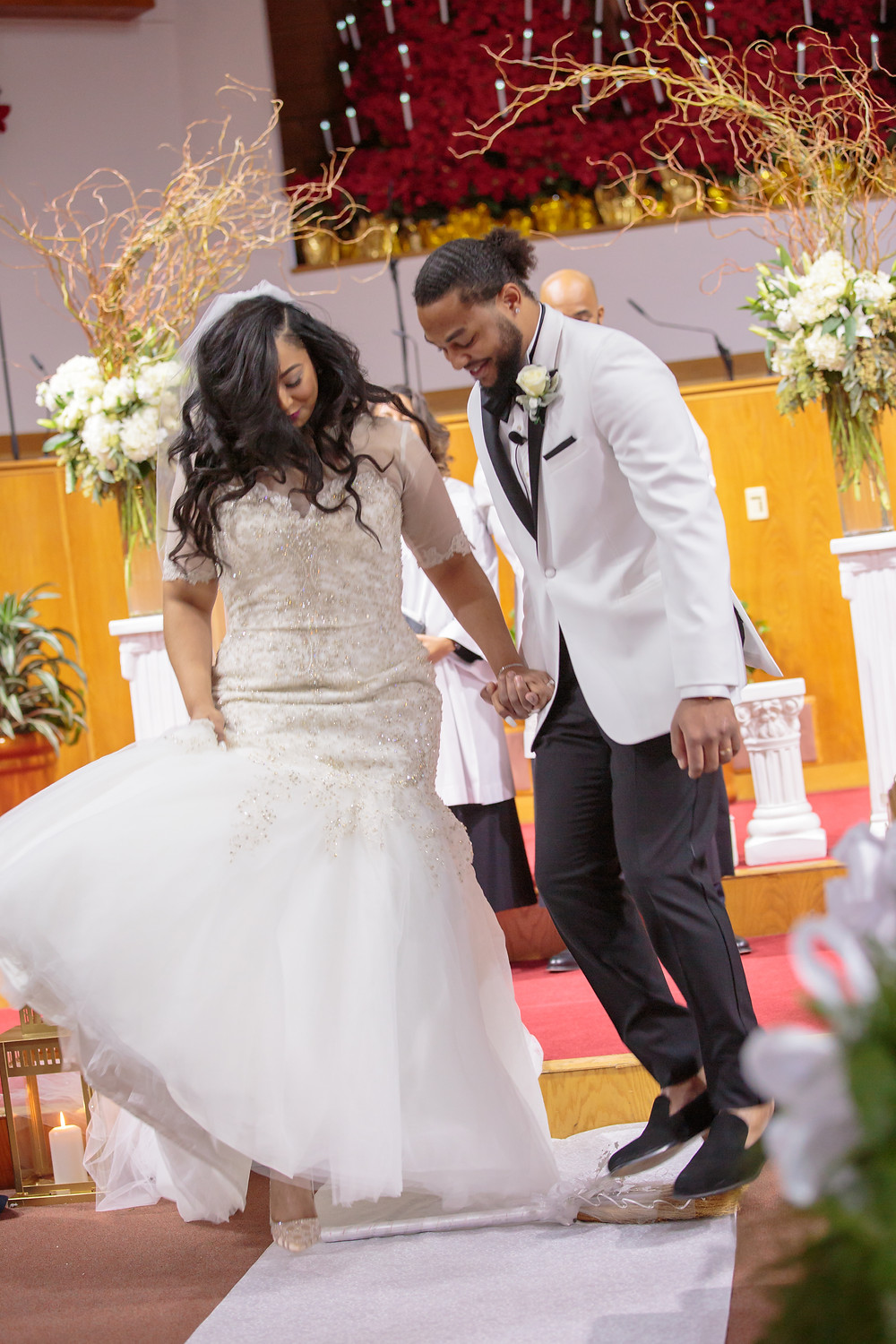 The bride and groom traditionally jump the broom after the wedding ceremony at the Alfred Street Baptist Church.