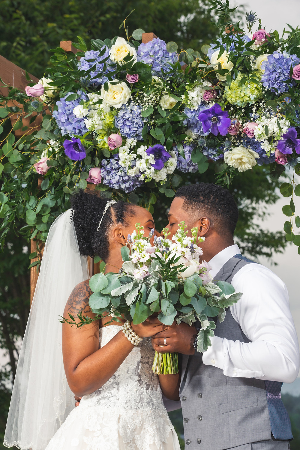 The bride and groom share a kiss behind the bouquet from The Faded Poppy at Crosskeys Vineyards in Mt. Crawford, Virginia.
