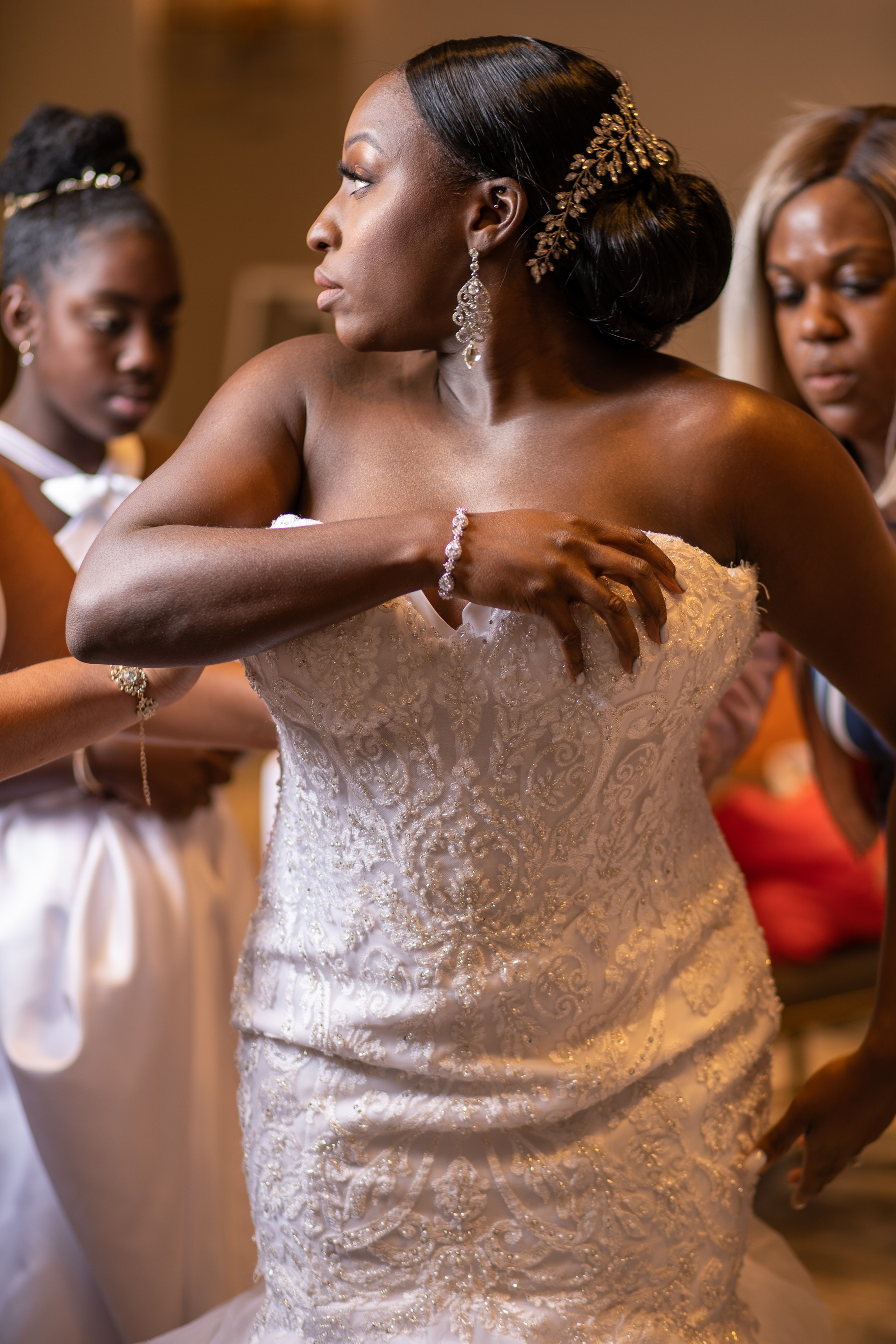 Bride puts on her dress with the help over her bridal party before the wedding ceremony at the Hilton Main in Norfolk, Virginia.