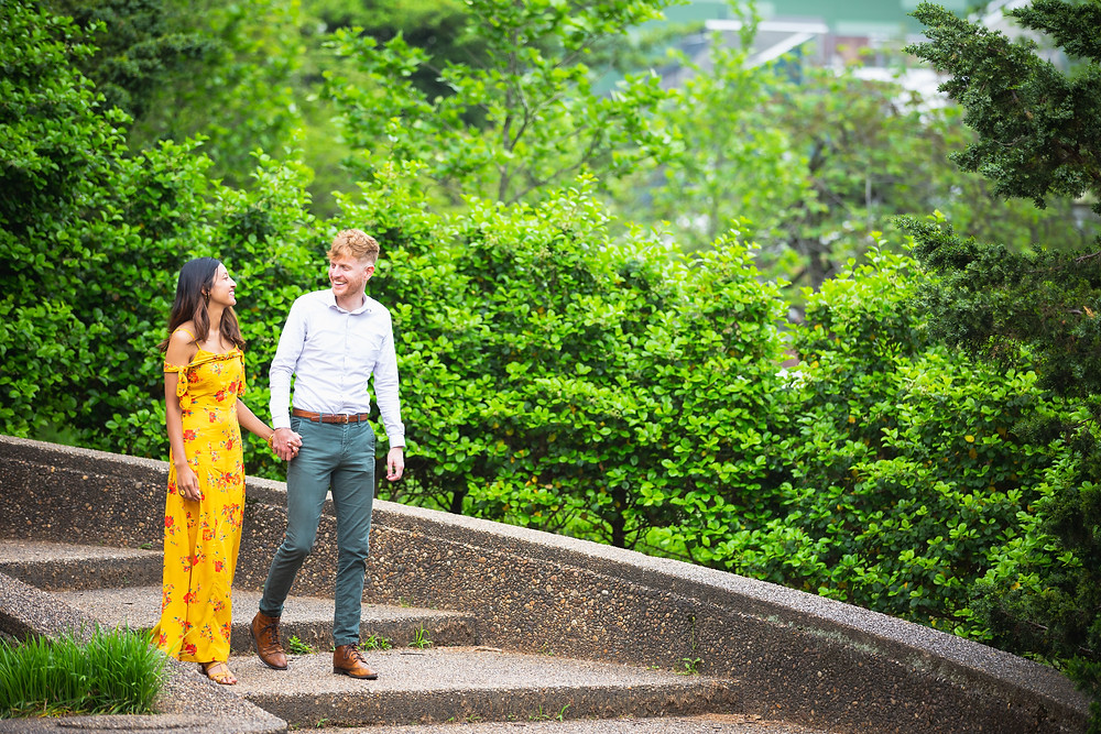 John and UK walk down the stairs while holding hands during the engagement session at Meridian Hill Park in Washington DC