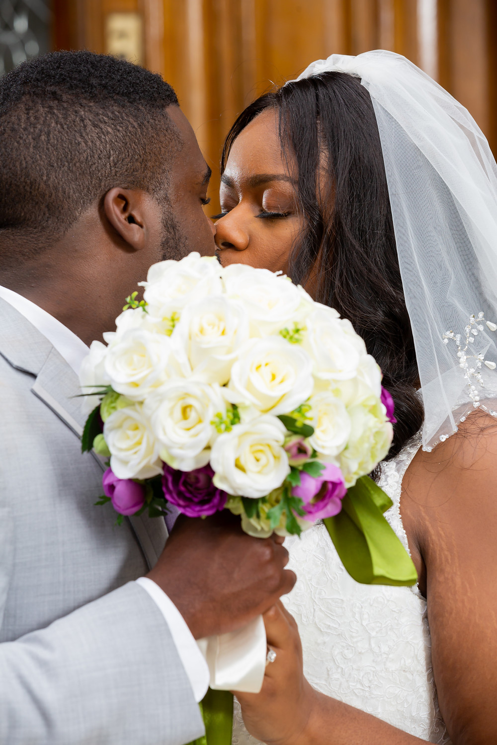 John and Jordyn sharing a kiss behind the bride's bouquet after the wedding in Fairfax, Virginia.