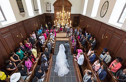 Bride walking down the church aisle with her long wedding dress train during a wedding ceremony at William & Mary College in Williamsburg, Virginia.