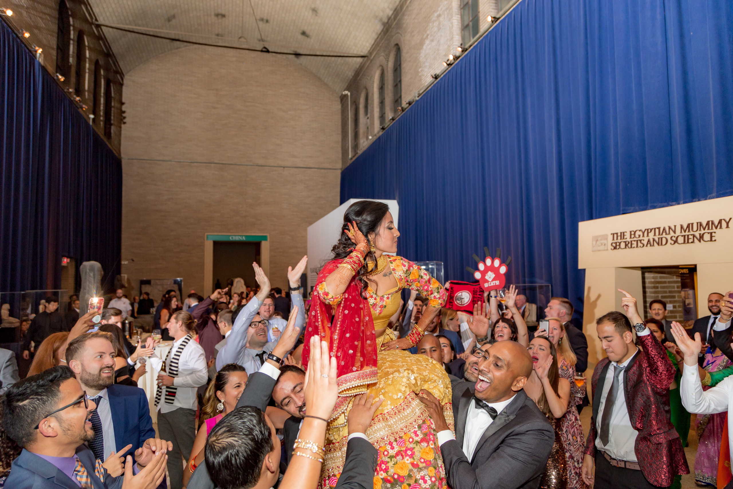 The bride's family hoist her to the air in celebration during the wedding reception at the Penn Museum in Philadelphia, Pennsylvania.