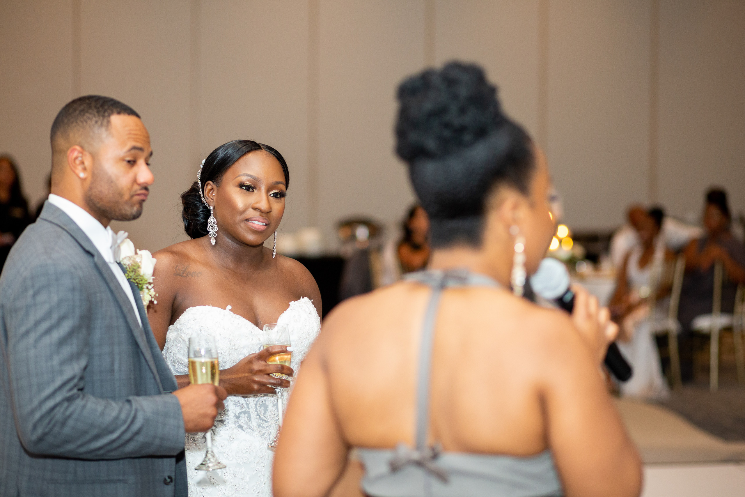 The bride and groom take in the maid of honor's speech and toast during the wedding reception at the Hilton Main in Norfolk, Virginia.