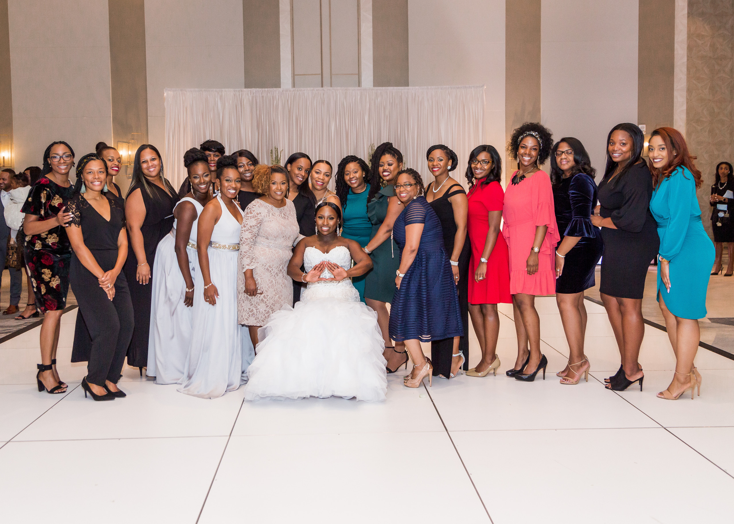 The bride poses with all of the ladies of Delta Sigma Theta Sorority Incorporated during the wedding reception at the Hilton Main in Norfolk, Virginia.