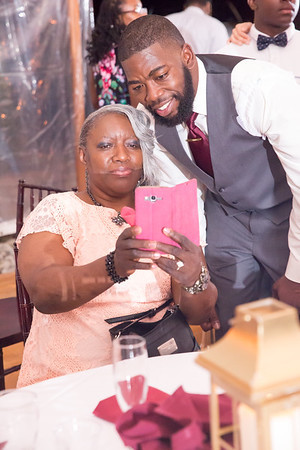 Groom and a guest posing for a photo on a cellphone.