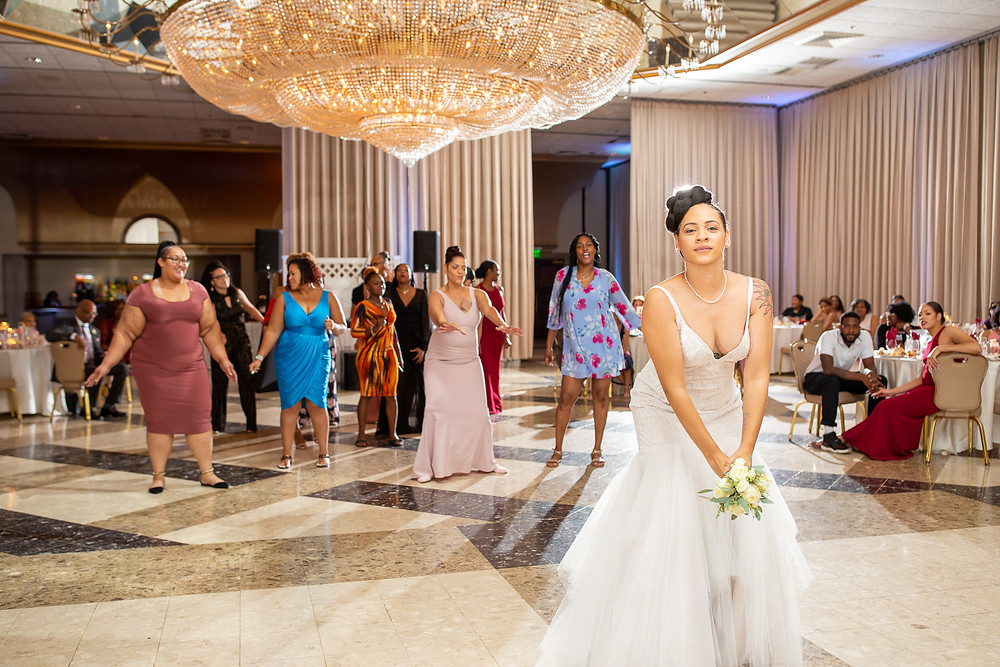 Bride tossing the bridal bouquet during the wedding reception at Martin's Crosswinds in Greenbelt, Maryland.