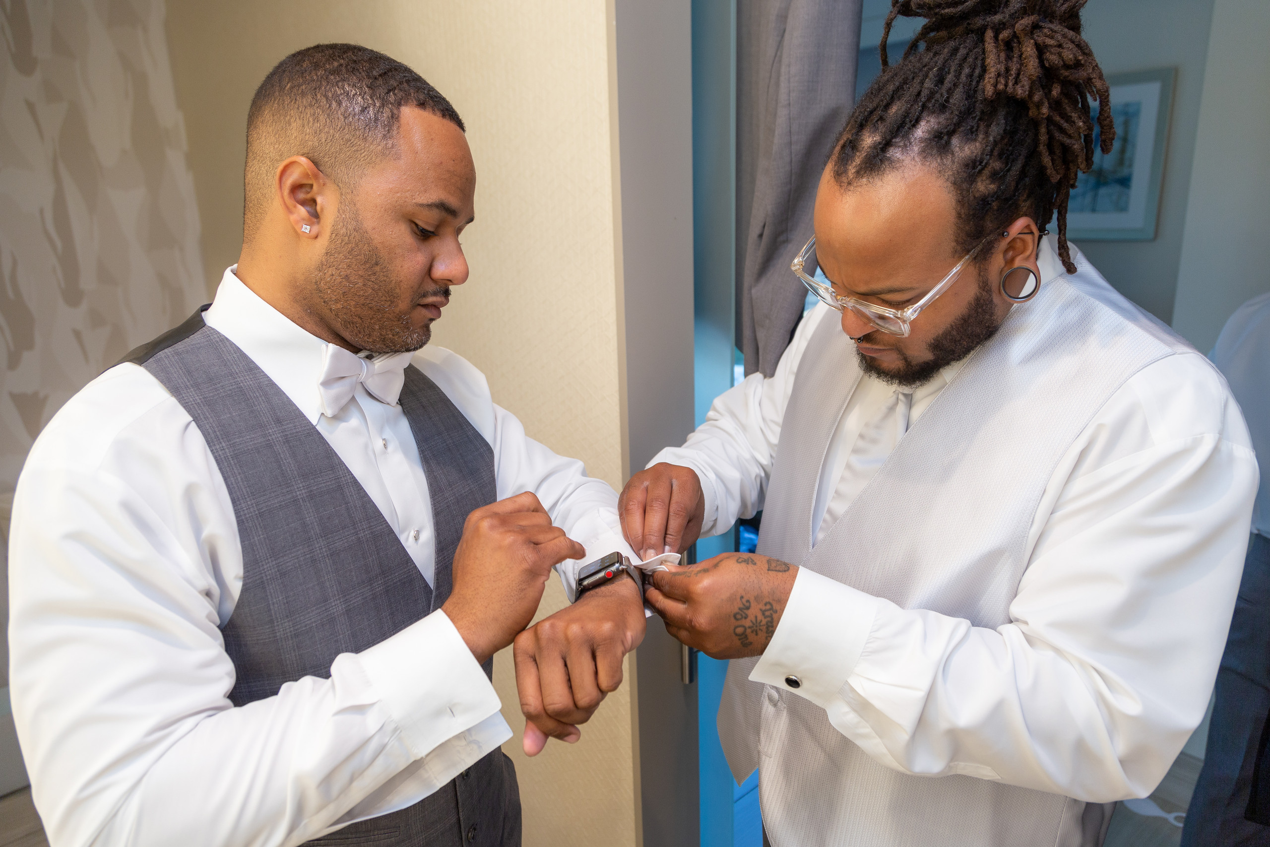 The best man helping the groom get ready before the wedding at the Hilton Main in Norfolk, Virginia.
