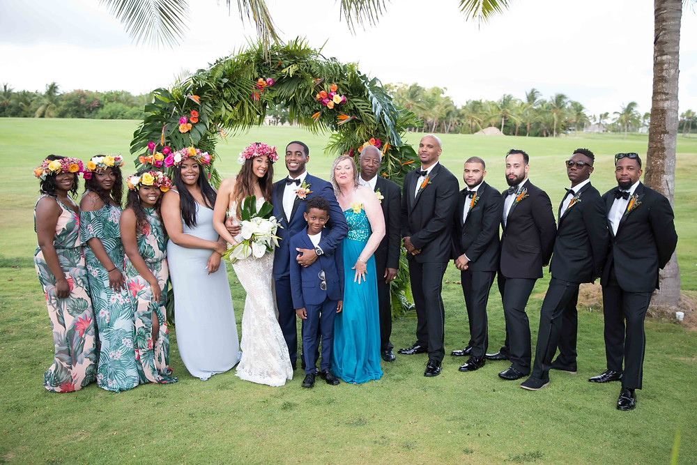 The wedding party and parents of the bride pose for a formal portrait after the destination wedding in Punta Cana, Dominican Republic.
