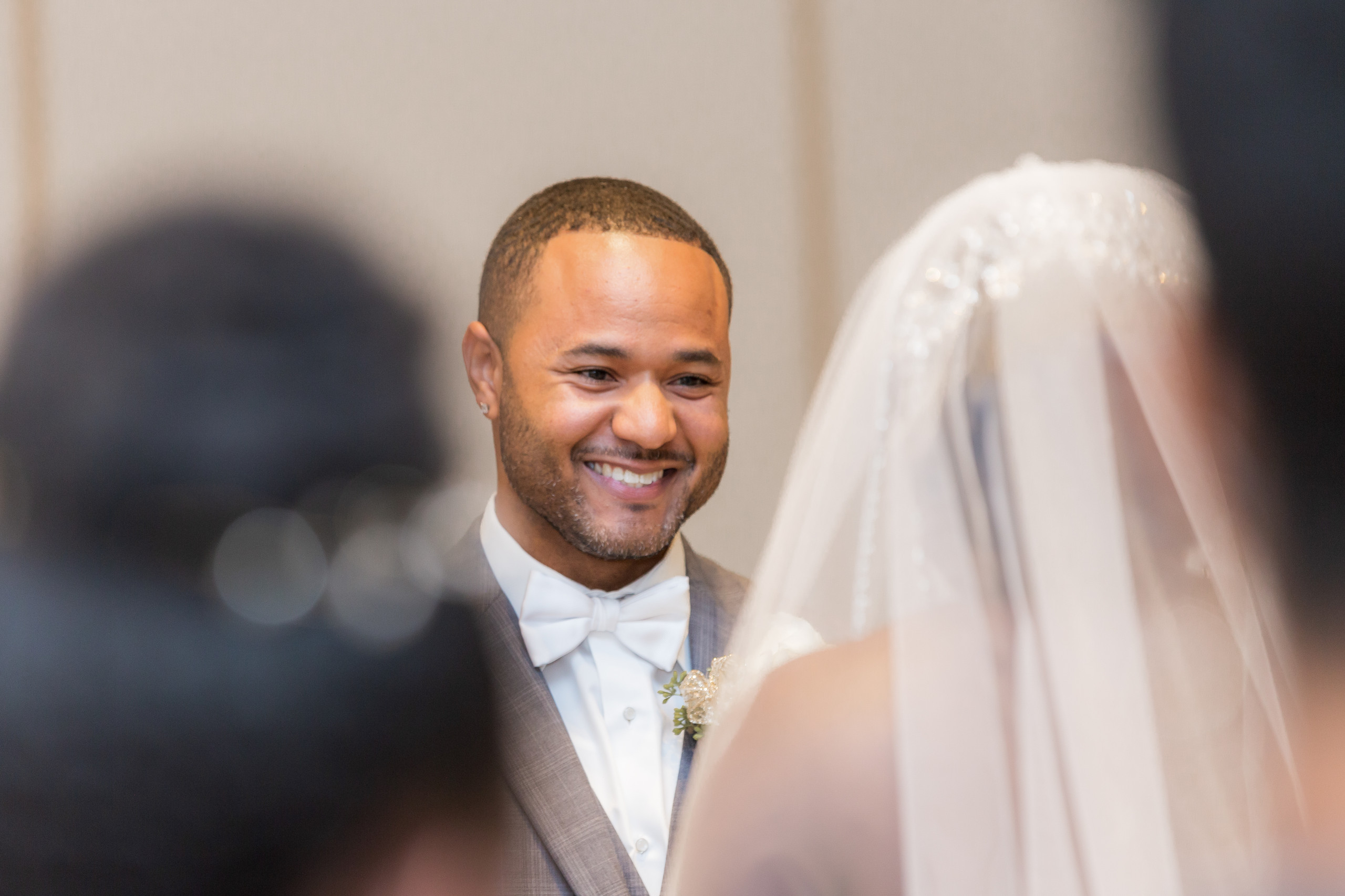 The groom smiles and gazes into the eyes of the bride during the wedding ceremony at the Hilton Main in Norfolk, Virginia.