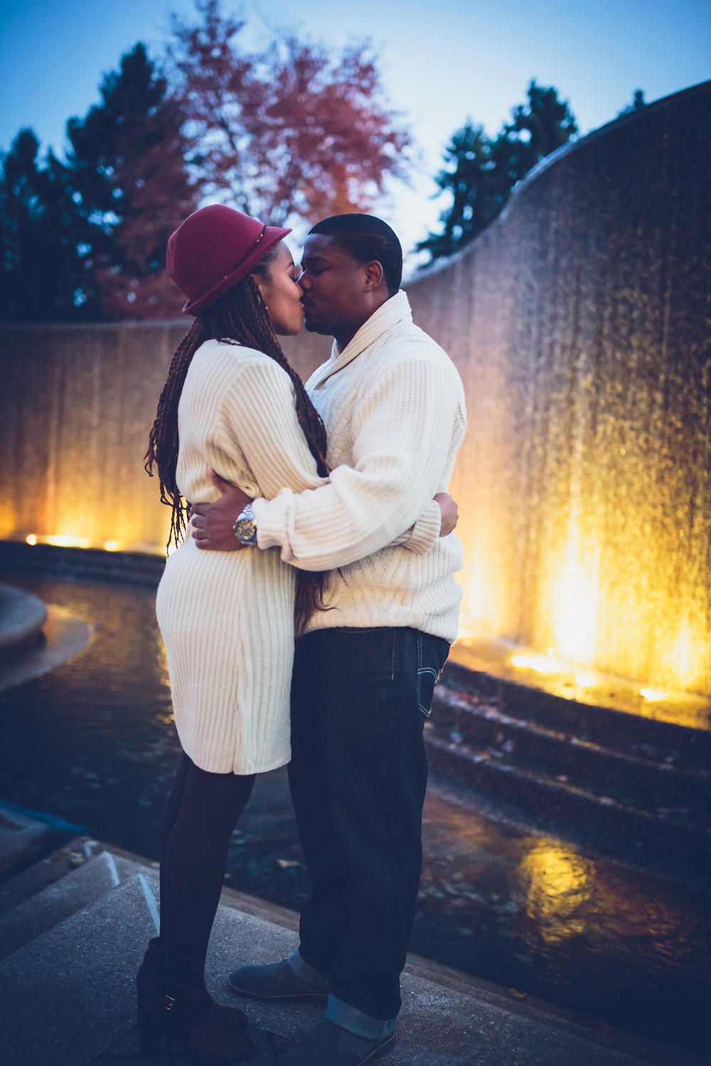 Tierra and Carl share a kiss by the Crystal City Water Park at their engagement session in Crystal City, Virginia.