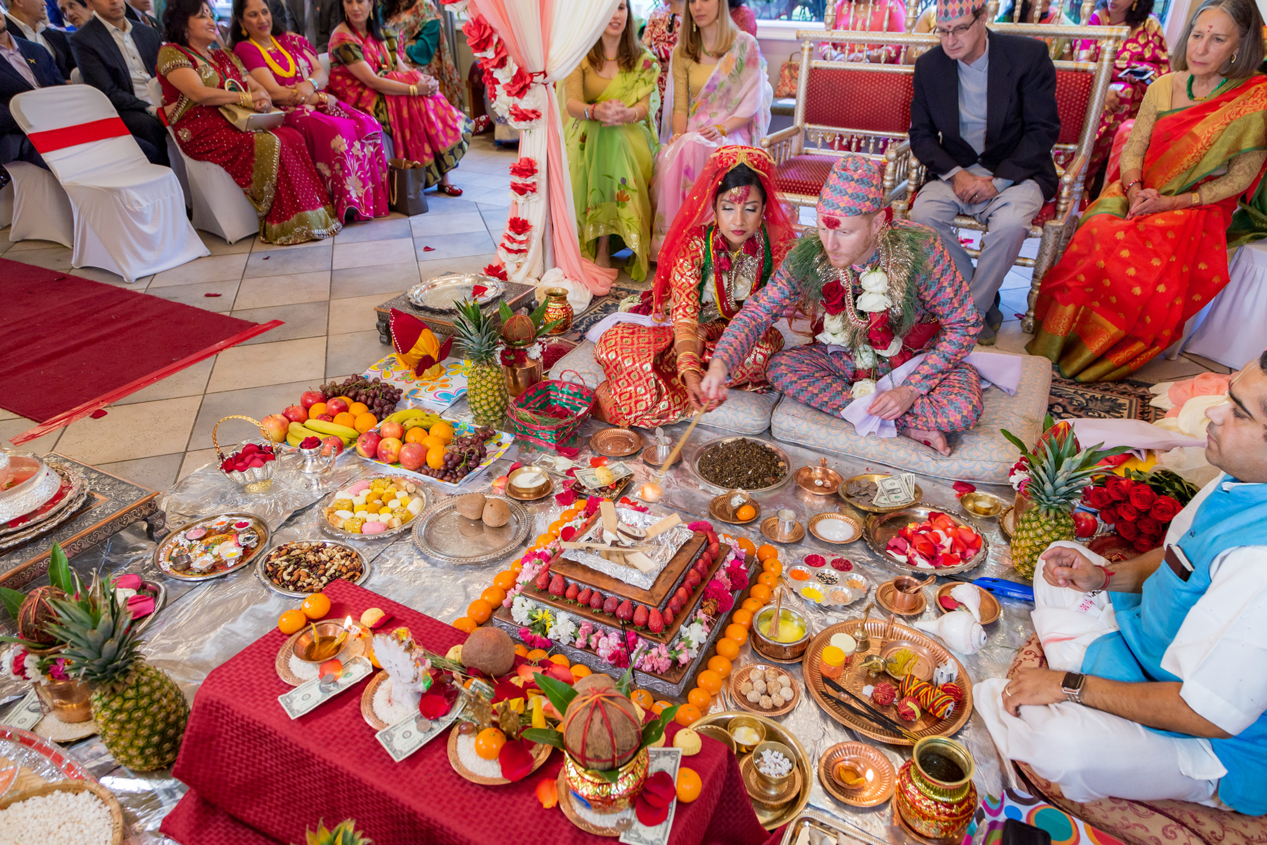 The bride and groom performing traditional rituals during the Hindu Ceremony at the ISKCON of DC in Potomac, Maryland.