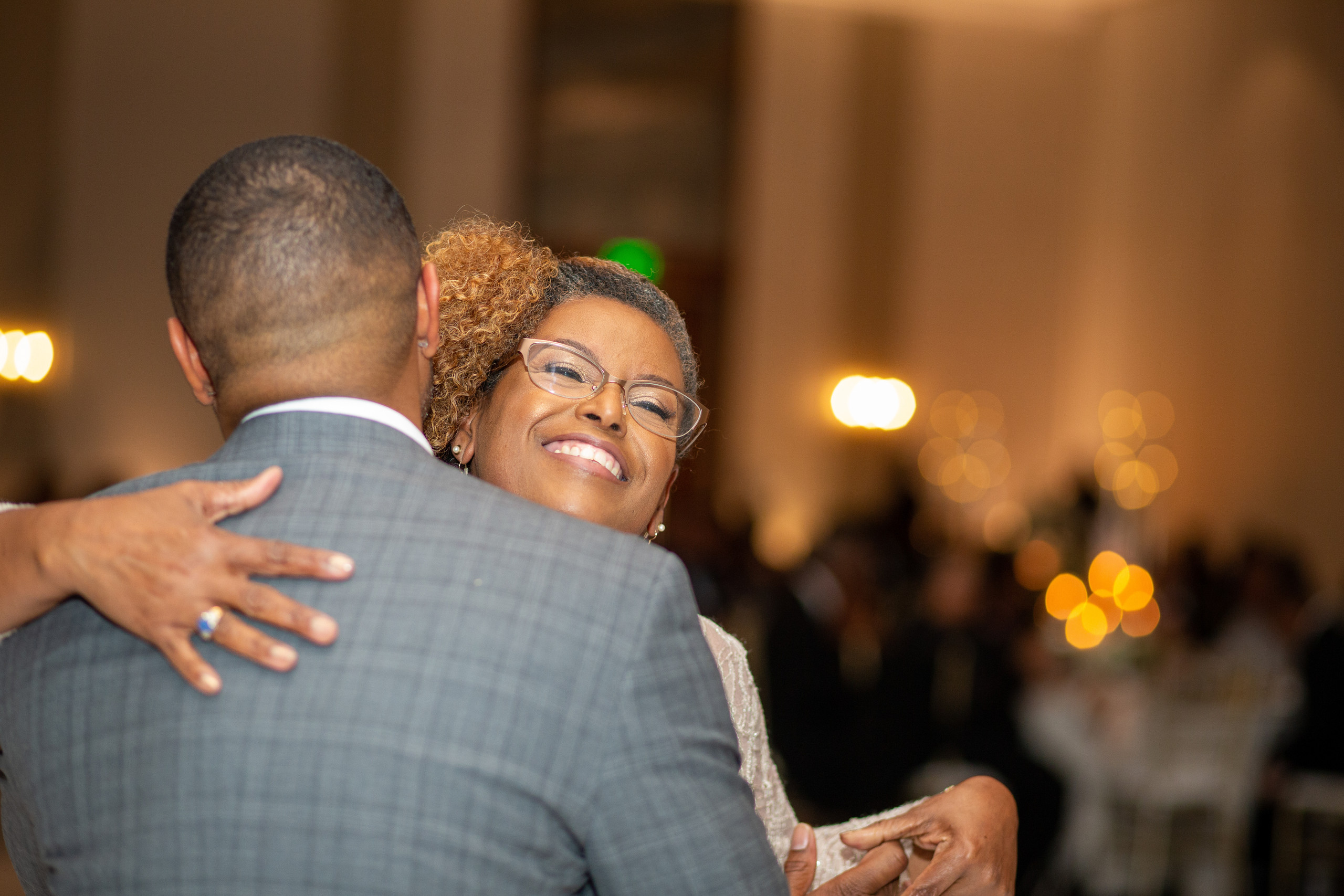 The mother of the groom shares pure joy while dancing with her son during the wedding reception at the Hilton Main in Norfolk, Virginia.