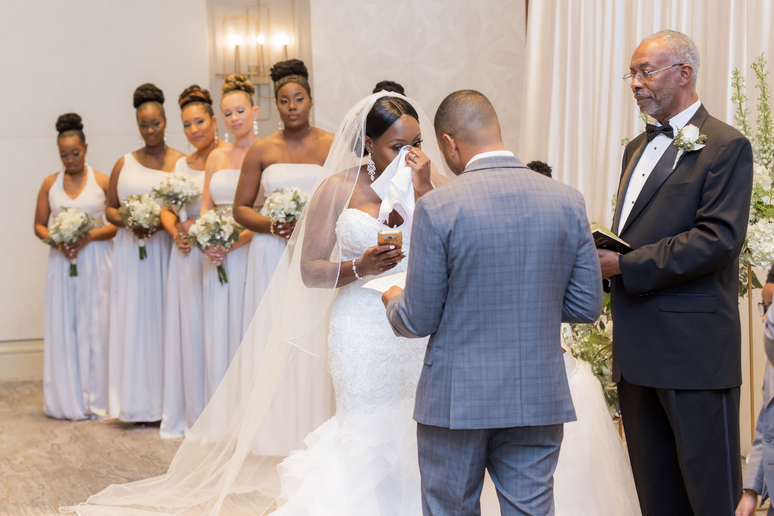 The bride tears up during the groom's vow recital during the wedding ceremony at the Hilton Main in Norfolk, Virginia.