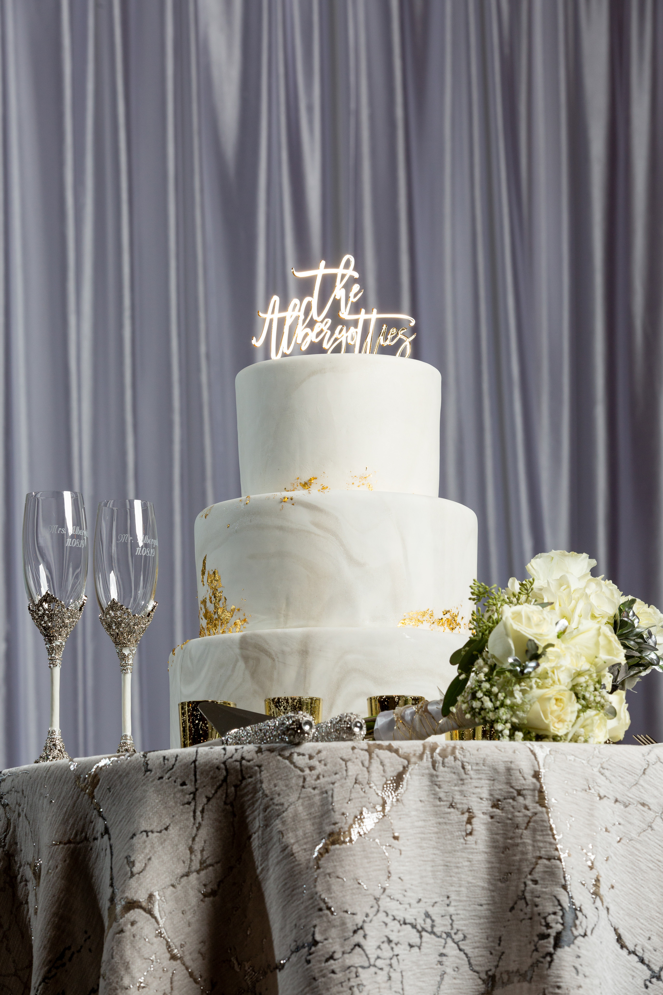 The stunning marble wedding cake, his and her flutes, and bride's bouquet on display during the wedding reception at the Hilton Main in Norfolk, Virginia.