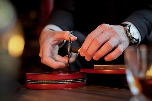 Men's hands cut a cigar with scissors. O