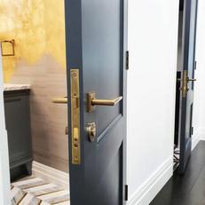 Double powder room doors with luxury door hardware.