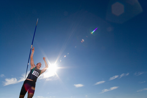 Male athlete throwing javelin at athleti