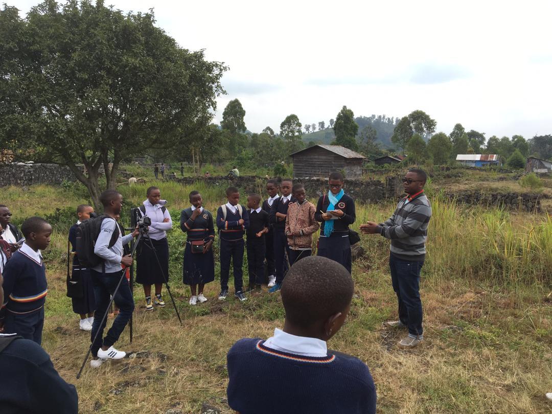 Goma Volcano Observatory Technologist Prosper Kamenyezi speaks to Cinquantenaire students on the deployment of CO2 sensors they built.