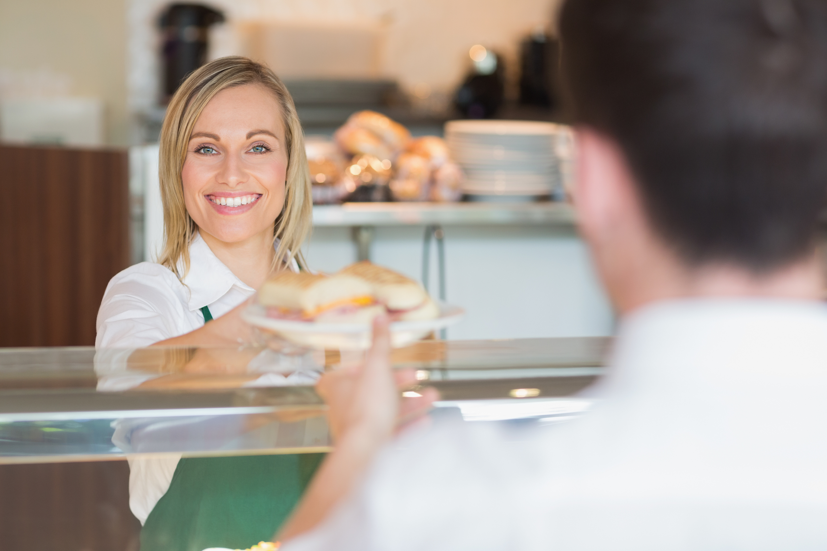 Portrait of female shop owner smiling while giving sandwich to customer in bakery