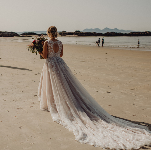 Bespoke Wedding Dress - Starry embroidery with soft dreamy tulle and twinkly glitter layered skirt on a beach.
