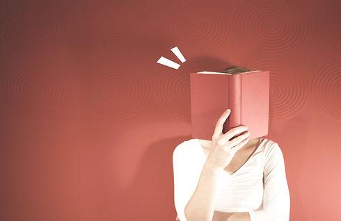 Frau in weißer Bluse steht vor einer roten Wand und liest ein rotes Buch