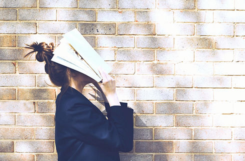 Eine junge Frau mit Dutt steht vor einer Mauer und legt eine Zeitschrift auf das Gesicht