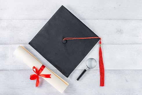 Schwarze Absolventen-Kappe mit Zertifikat und Lupe.jpg