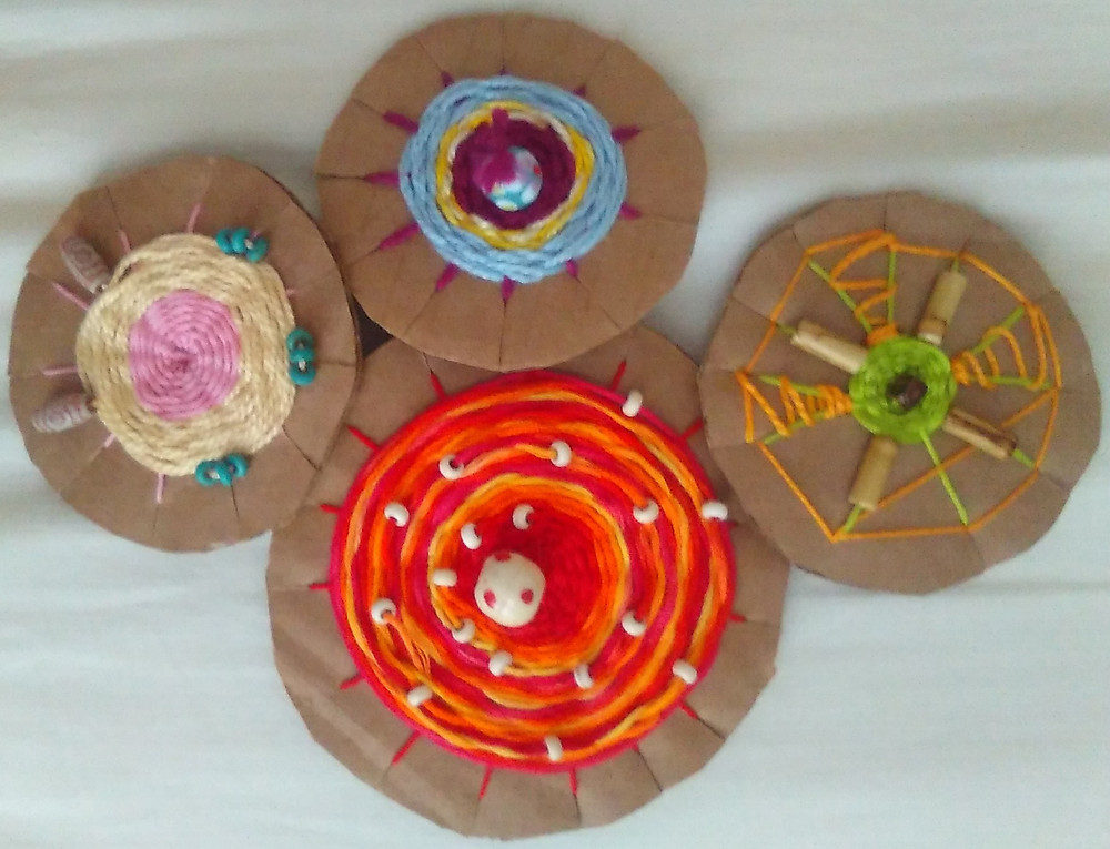 Four corrugated cardboard circles embellished with colored yarn and beads.