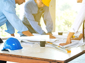 Selective focus of helmet with engineer team and worker looking paper plans at constructio