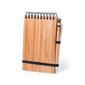 Libreta de anillas  con tapas rígidas de bambú y bolígrafo a juego, también en bambú. De tamaño compacto, con elástico de cierre en elegante color negro. Incluye 80 hojas con disposición a una raya y diseño eco. Bolígrafo con cartucho jumbo y tinta azul.