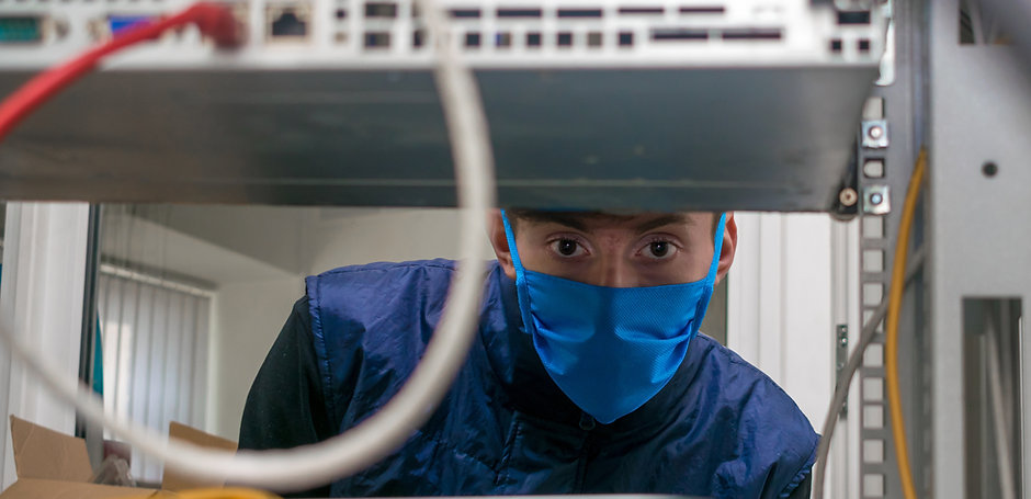 A technician in a medical mask works in