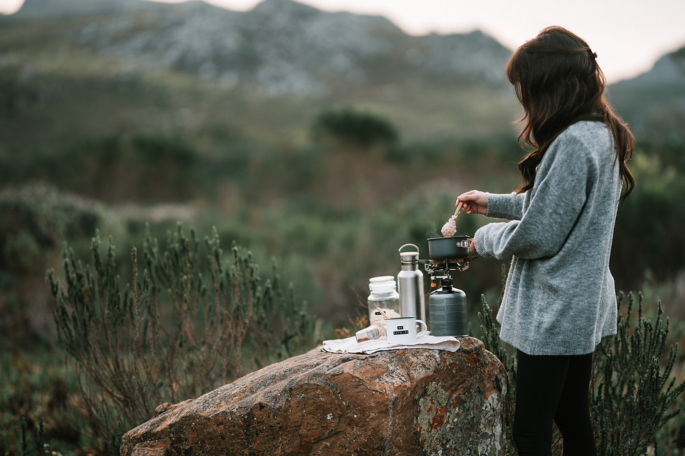 woman-cooking-on-log-in-backcountry