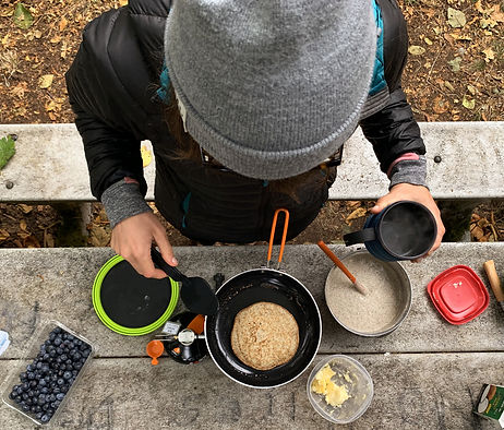 Woman-standing-over-backcountry-stove-cooking-pancakes