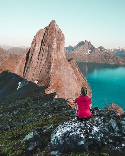 Woman-sitting-on-rock-near-Norwegian-fjord