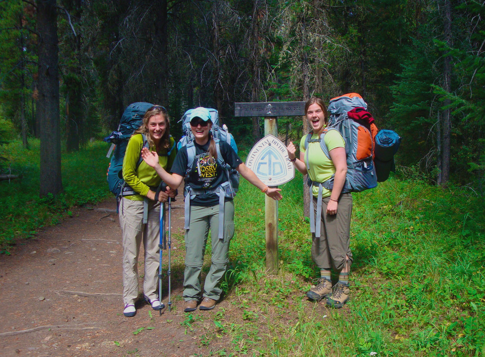Three-women-standing-by-sign-before-backpacking-course