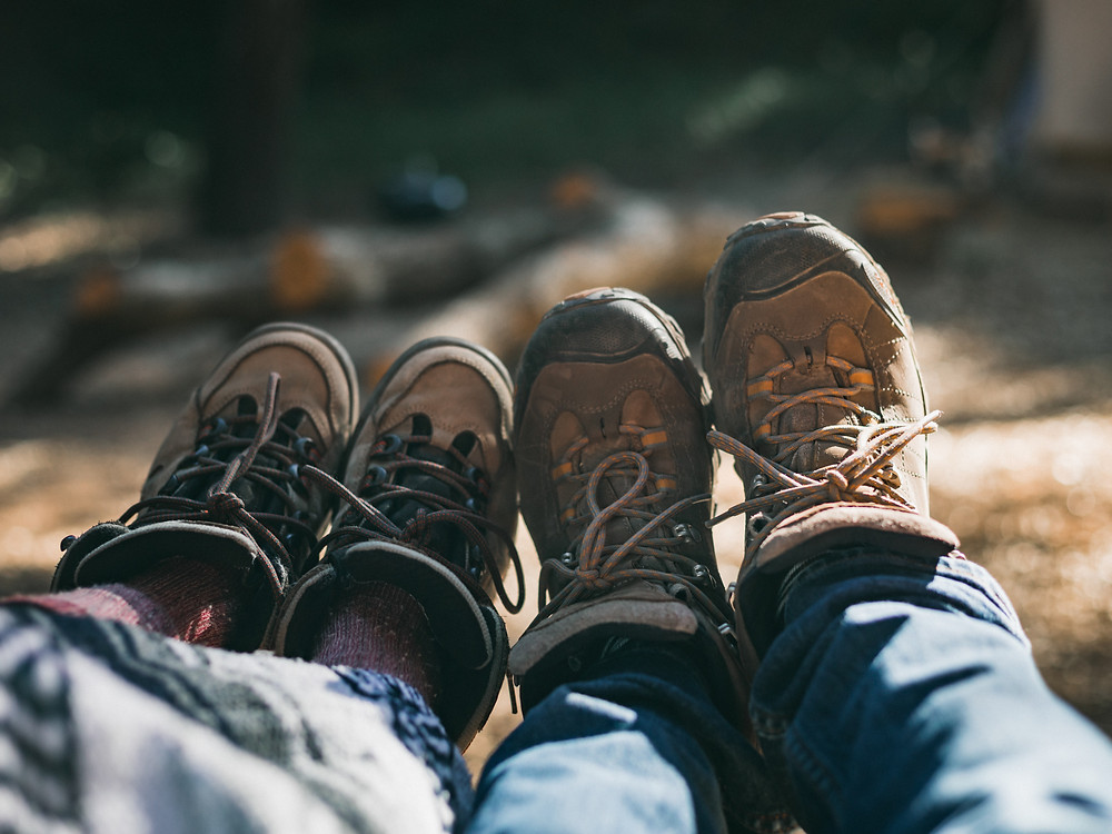 two-pairs-of-feet-in-hiking-boots-resting-against-each-other