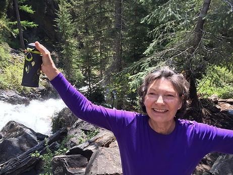senior-woman-smiling-next-to-waterfall