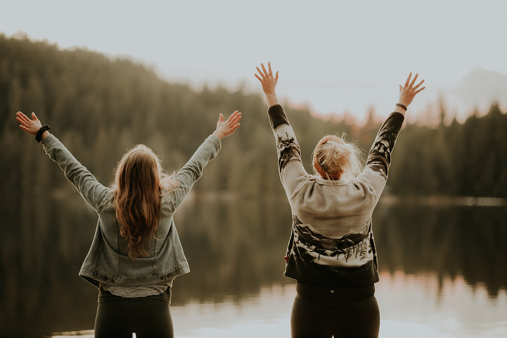 Two-women-with-arms-outstretched-on-lakeshore