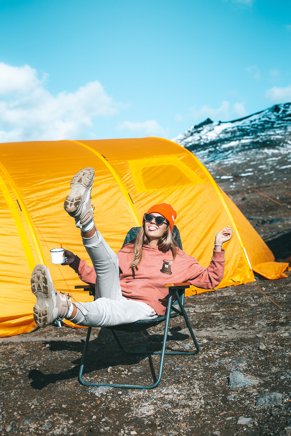 woman-leaning-back-in-camping-chair-and-smiling-with-tongue-out