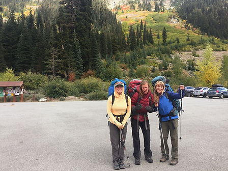 Three-woman-smiling-in-parking-lot-before-backpacking