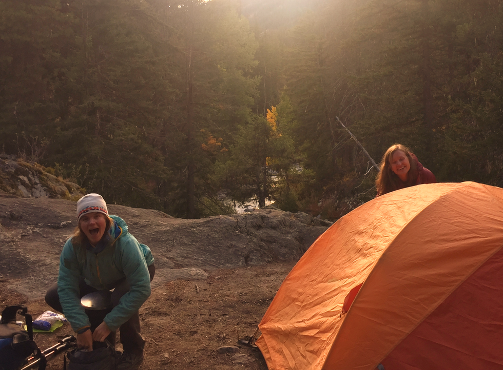 Two-woman-setting-up-tent-evening-time