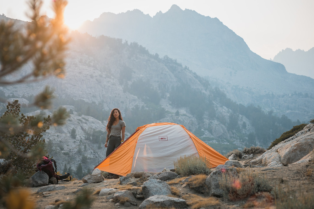 woman-standing-next-to-tent-in-mountainous-backcountry